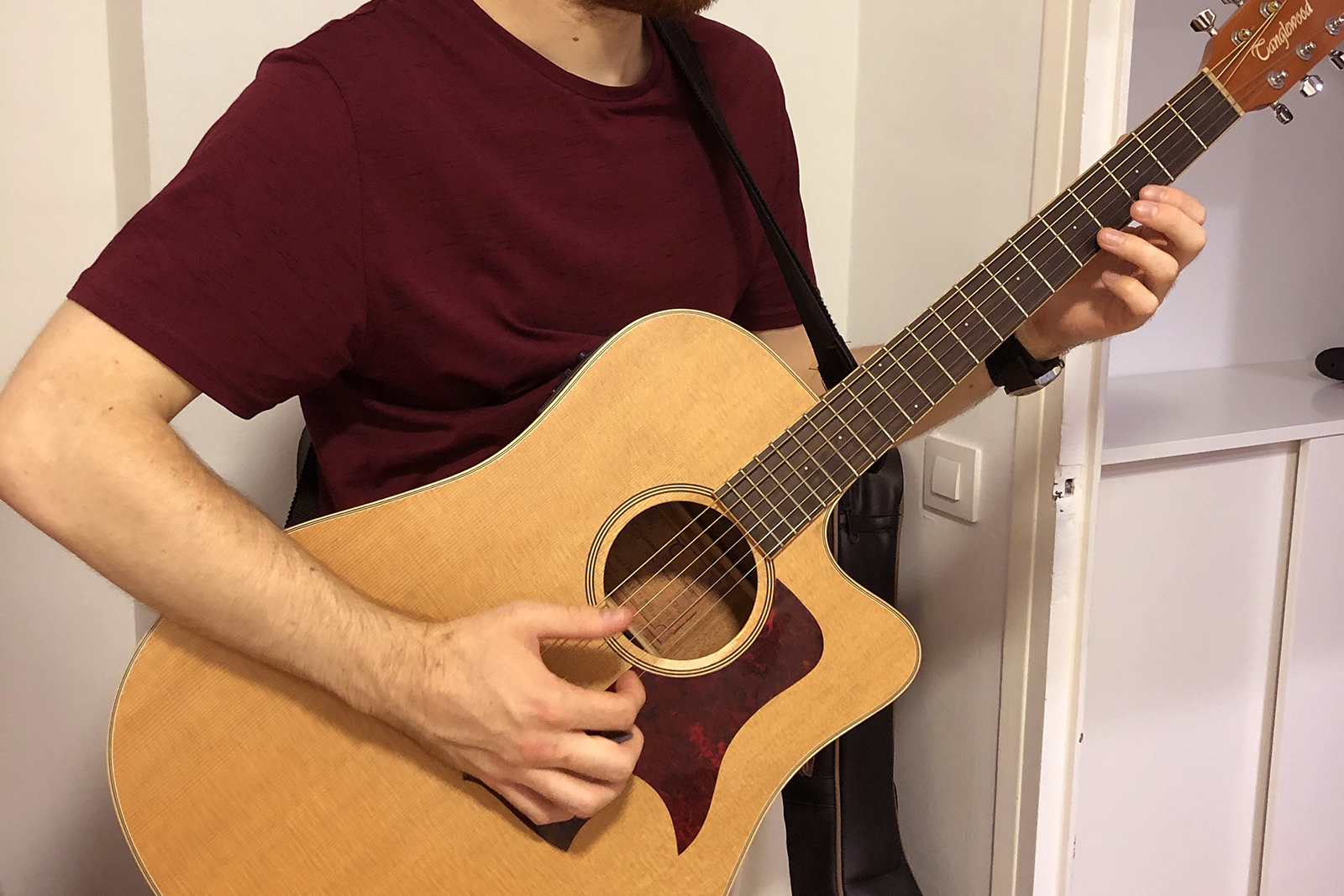 Man playing an acoustic guitar. Playing a musical instrument can have physical, mental, and emotional benefits.