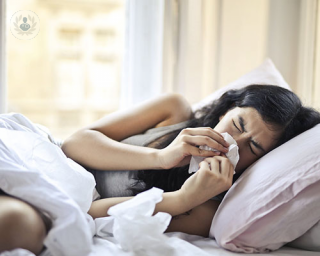 A woman in bed blowing her nose.