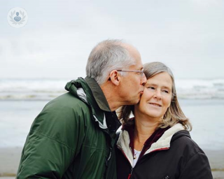 Older man kissing older woman on the cheek on the beach.
