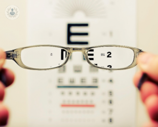 Holding glasses up to an eye test