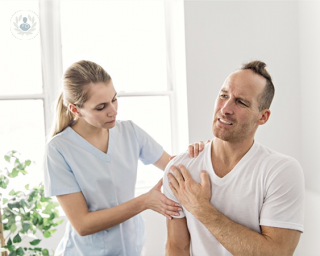 Healthcare worker attending a man with a painful shoulder