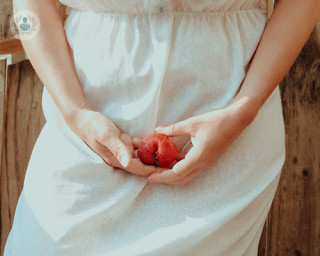 women holding strawberry in front of her genital area. Women can experience different skin conditions of the vulva.