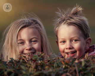 Two children are looking at the photographer. They are smiling and playful, hiding behind some grass.