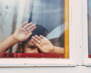 Child looking out the window with his hands on the glass