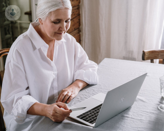 Elderly woman sat at a table on her laptop