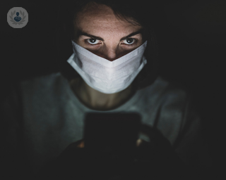 A woman wearing a covid-19 face masks looks up to the camera.