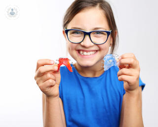 A young girl about the age of 8 years old is holding two small apparatuses in front of her. These apparatuses are braces that are placed inside the mouth behind the teeth in order to prevent and/or correct future teeth and jaw issues.