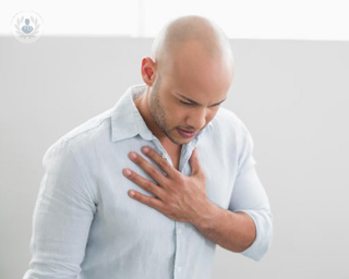 Man with chest pain holding his chest