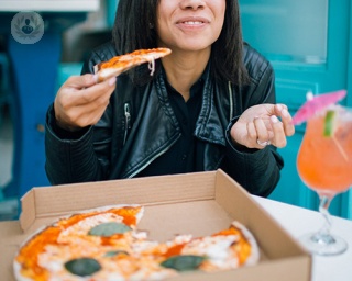 woman eating pizza and smiling