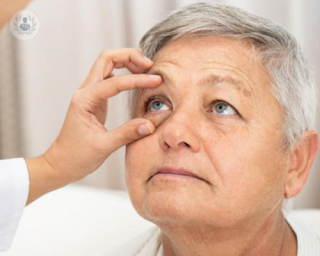 Woman with eye held open by dr examining