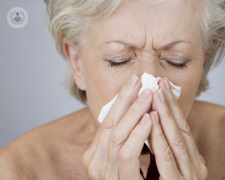 older lady blowing her nose into a tissue