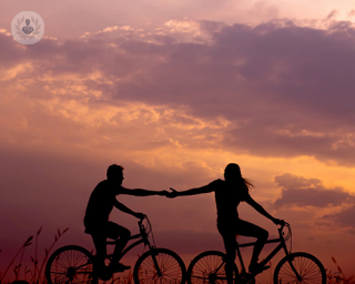 People leisurely cycling at sunset