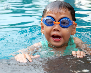 Chid wearing blue goggles in a pool
