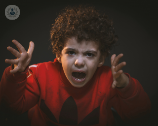Toddler looking angry and shouting using his hands