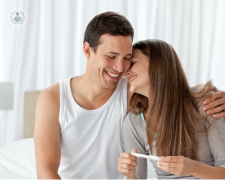 Man hugging woman on a bed smiling and holding a pregnancy test