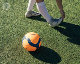 Child stretching their heel next to a football