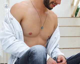 Man sat down with his shirt unbuttoned showing his chest