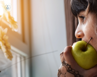 Woman eating an apple and looking out the window