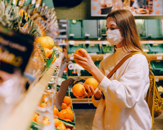 Woman wearing a mask in a supermarket picking up oranges