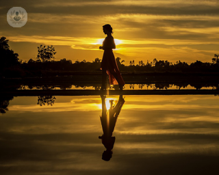 Woman walking by yellow lake