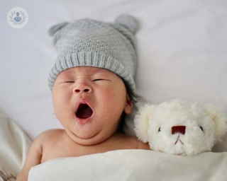 Baby yawning in cot, wearing a hat.