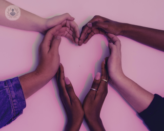 Lots of hands coming together forming the shape of a heart on a pink background