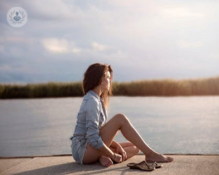 Woman sitting by lake. Some women experience reccurent UTIs, which the Uromune vaccine system can help treat.
