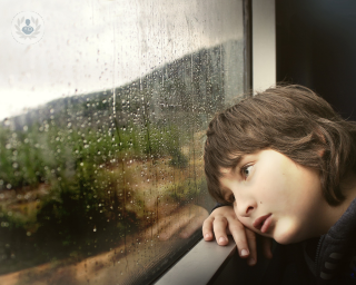 Boy appearing sad and looking out of the window of a train