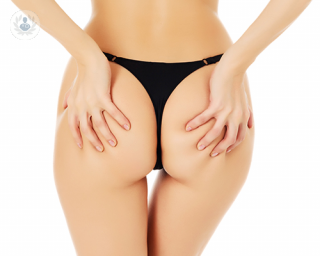 The photo is angled to directly face a woman's buttocks. She has one hand on each bum cheek and is gripping the fat.