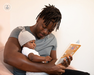 Father holding his baby and reading a story from a book