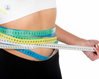 Waist of woman who has lost weight with tape measures