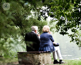 Two elderly people sat on a bench looking at a lake