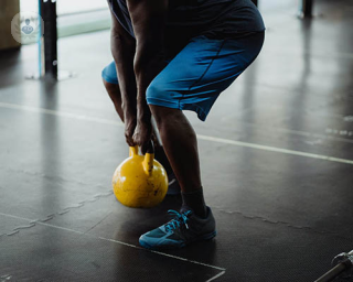 A man uses a dumbell to exercise, putting pressure on his knees.