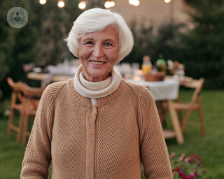 An elderly woman smiling and looking at the camera