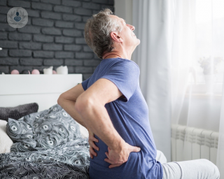 Elderly man sitting on his bed and holding his lower back in pain