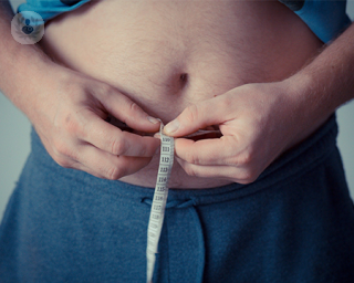 A man's overweight stomach with a tape measure around it.