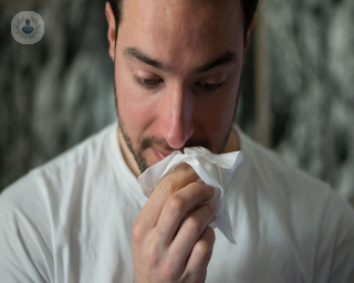 A man with sinus problems blowing his nose