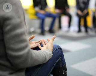 The focus is on the hands of a person who is talking to a group of people who are all sat on chairs in a circle, perhaps in a dialectical behavior therapy session. This is beneficial for many with borderline personality disorder.