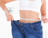woman in oversized jeans measuring waist