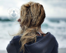 Blonde haired woman stood by the sea with back to camera, windy