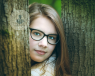 girl in glasses, head between to trees