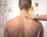 shirtless back of a man, with a doctor hand on shoulder