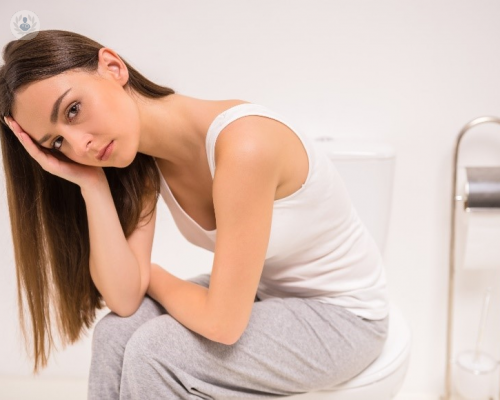 Woman looking concerned and sat on the toilet