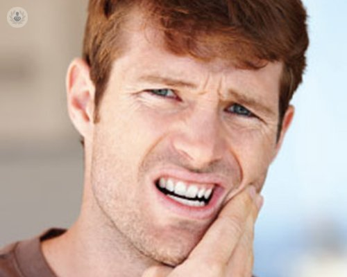 man with pain in mouth holding cheek