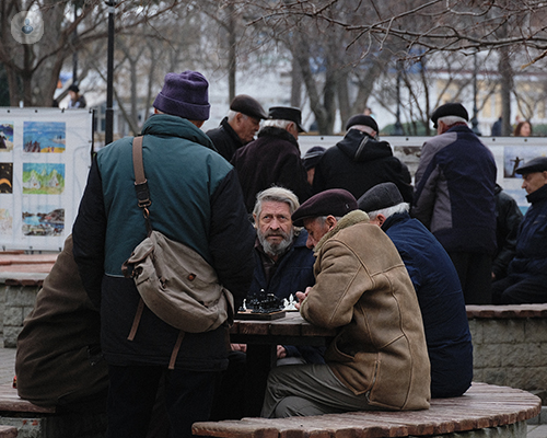 Group of old men sitting around a table in a park