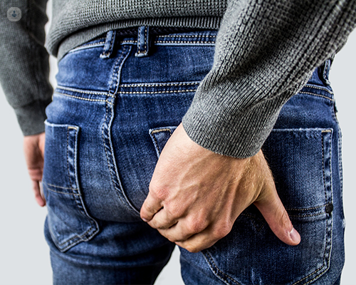 An image of a man's buttocks. He is wearing jeans and has his hand over his buttocks. He is scratching it in discomfort, perhaps due to haemorrhoids (piles) or rectal prolapse.