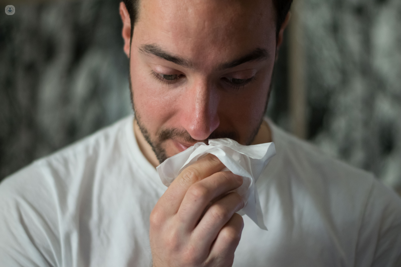 Man blowing his nose. Having a blocked or runny nose is a common symptom of the common cold.