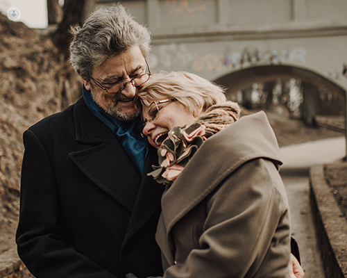 An elderly couple laughing and hugging while outdoors.