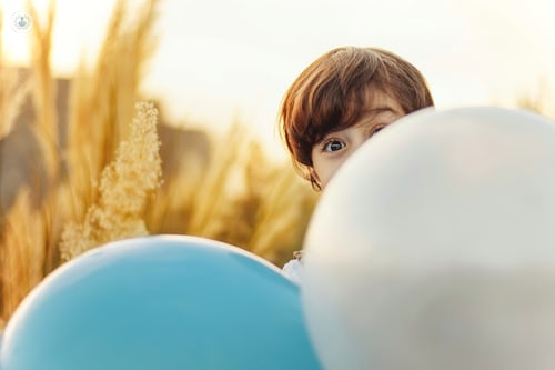 Little boy peeping past a balloon