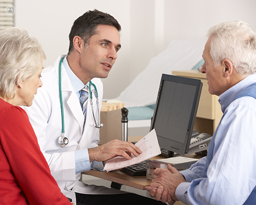 A doctor is having a consultation with an elderly patient and his partner. He is reading the results of an examination, perhaps a FibroScan.
